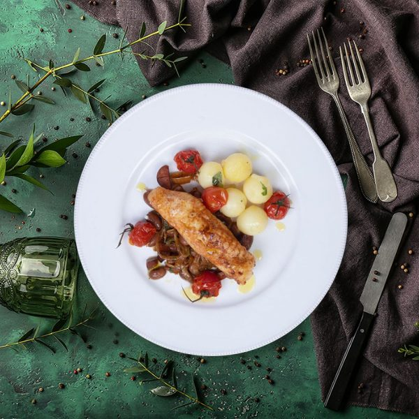 cajun monkfish with chorizo and cherry tomatoes on green and purple tablecloth