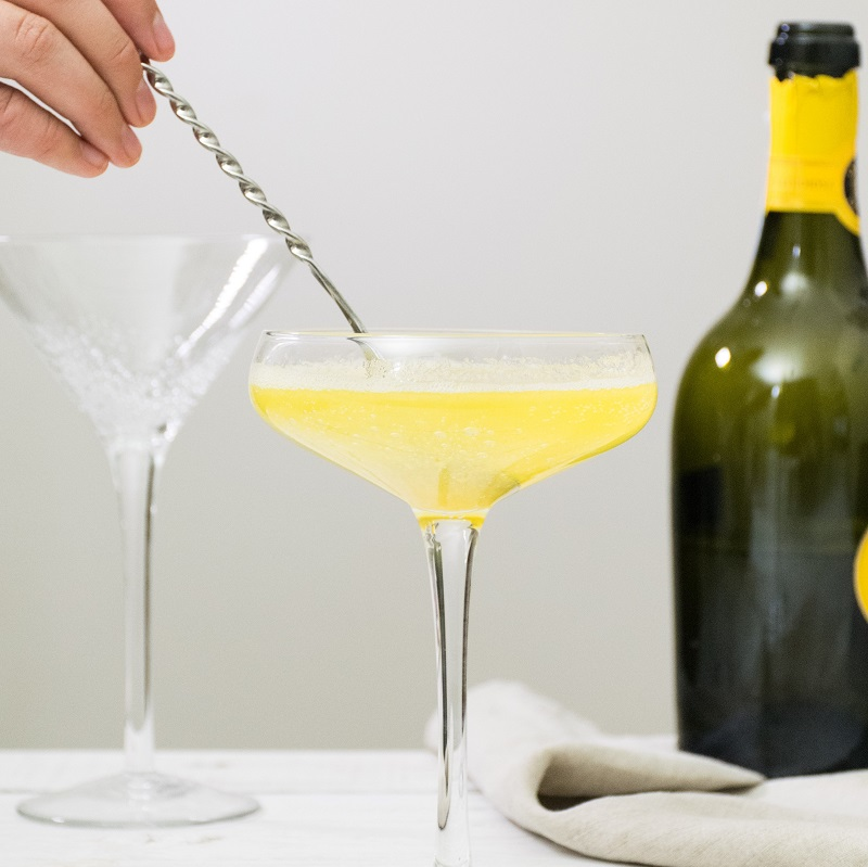 hand mixing a bellini cocktail against a white background