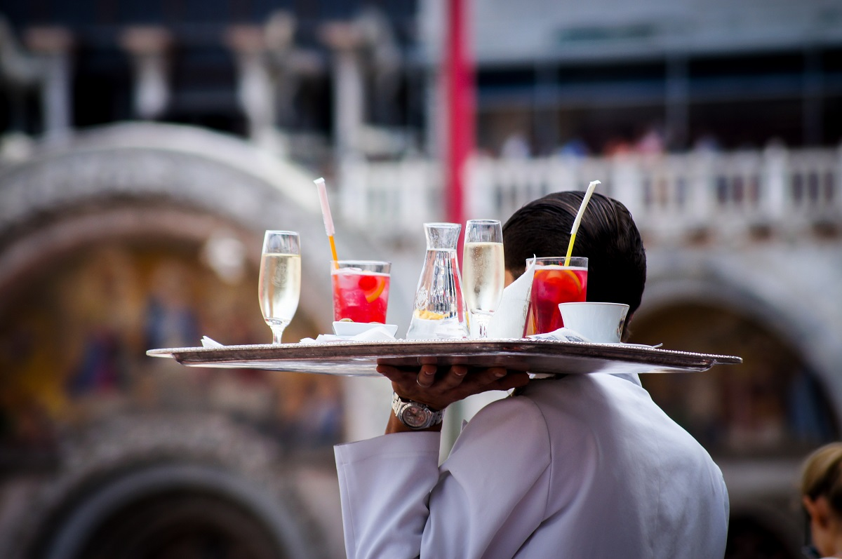 Waiter in Venice carries a tray of cocktails through st mark's square