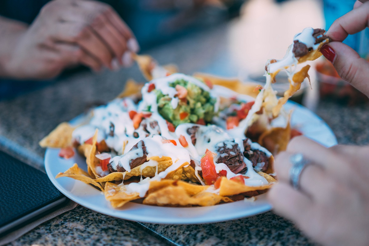 friends enjoying a plate of loaded nachos around a table